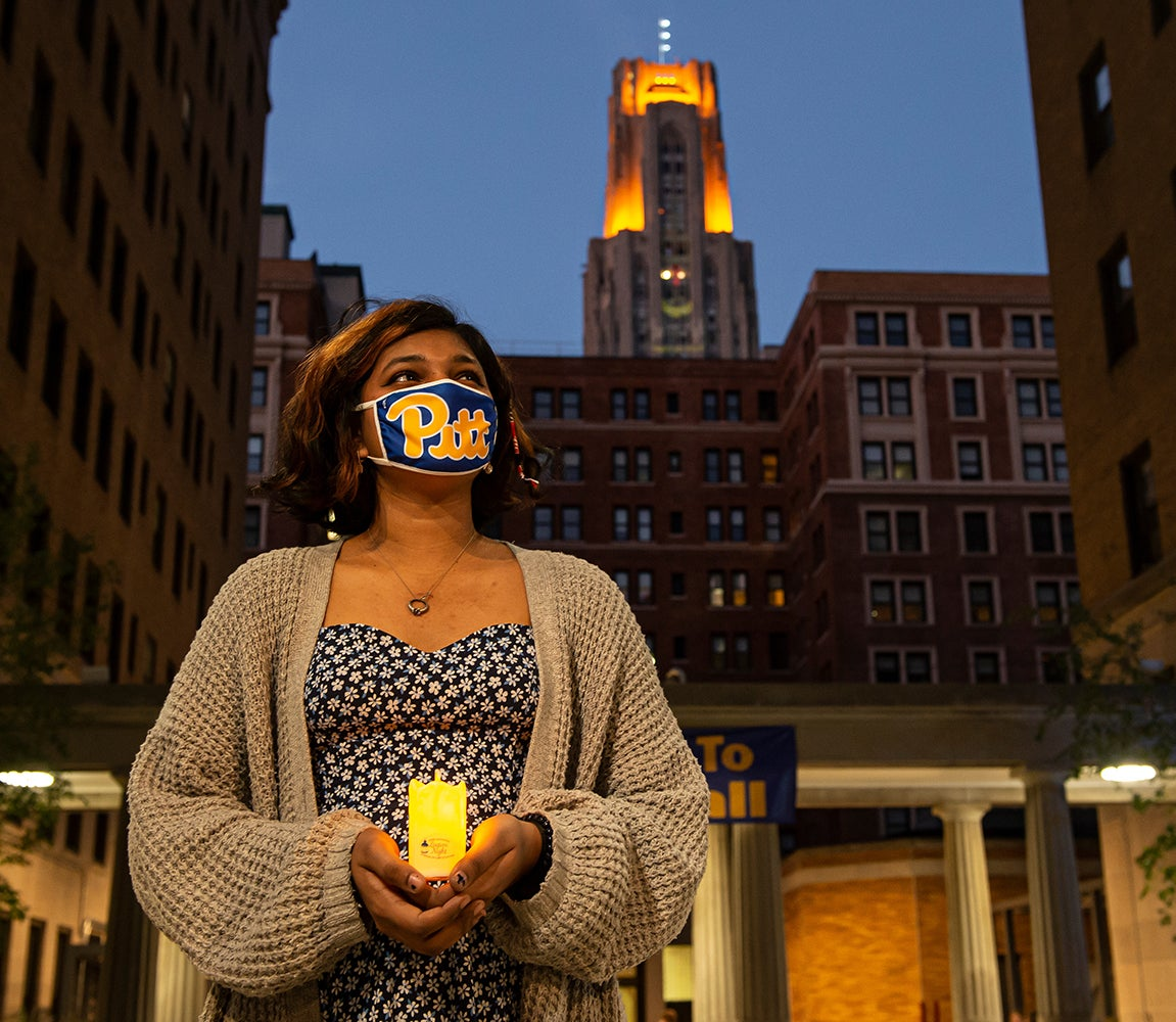Student wearing tan cardigan and floral dress holds her LED-powered lantern and wears her Pitt script mask in the Quad, the Cathedral lights on in the background