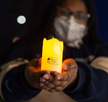 A Black woman in face covering holds out LED lantern to camera