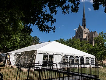 fenced-in line leads to white tent, Heinz Memorial Chapel in background