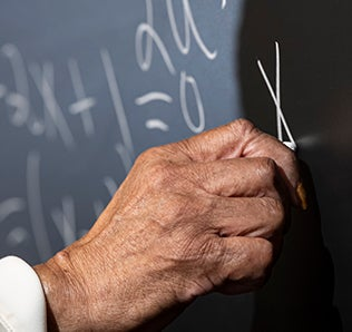 "Hand writes an ""x"" with white chalk on blackboard"