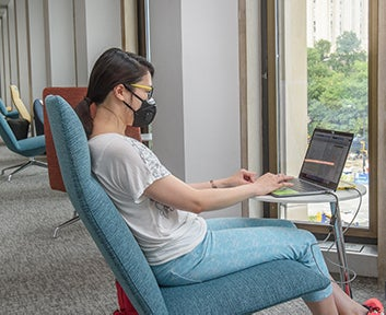 masked student sits in turquoise chair working on laptop and looking out onto Schenley Plaza