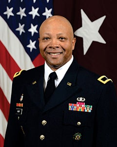 U.S. flag in background, wearing in formal uniform with tie, U.S. pin on one lapel and an American flag pin on the other lapel