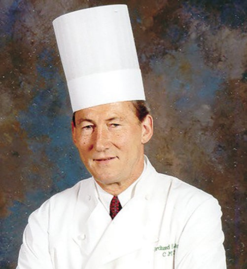 man wearing white coat, tie and chef's hat