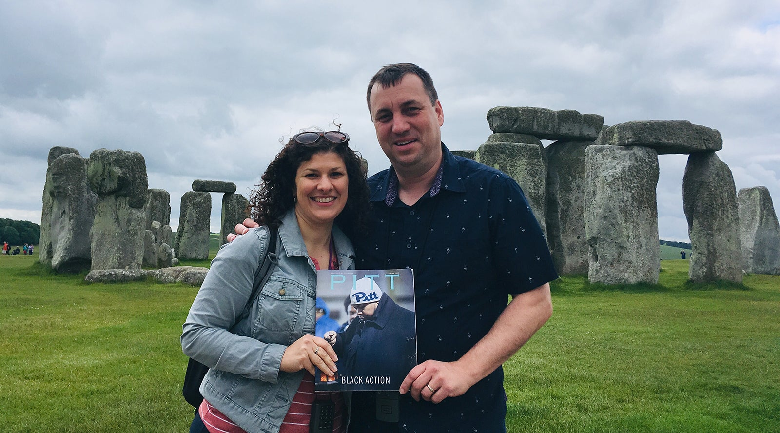 dark-haired main and woman hold Spring 2019 issue of Pitt Magazine in front of Stonehenge