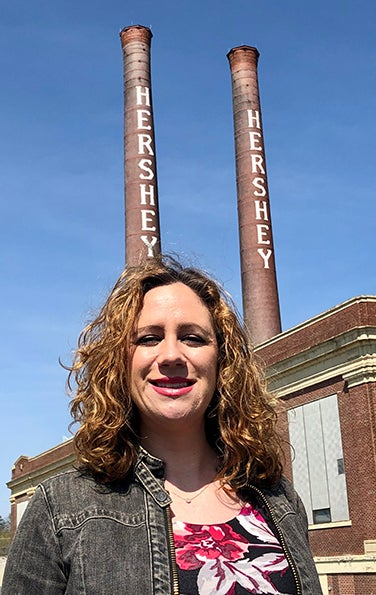 Tara Kennedy Griffiths in floral shirt and jean jacket in front of old Hershey factory stacks