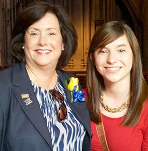 Karen, wearing a blue blazer and patterned blouse with a yellow rose pinned to her lapel, with daughter Maggie, in a red dress, at
