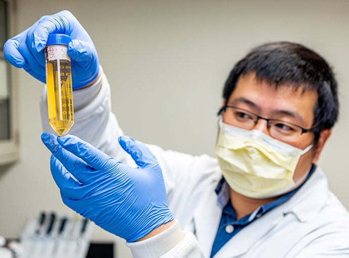 Masked scientist in blue gloves holds amber-colored measuring tube