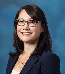 Nancy Merritt in navy blue blazer with teal photo background, wearing glasses and multi-chain necklace
