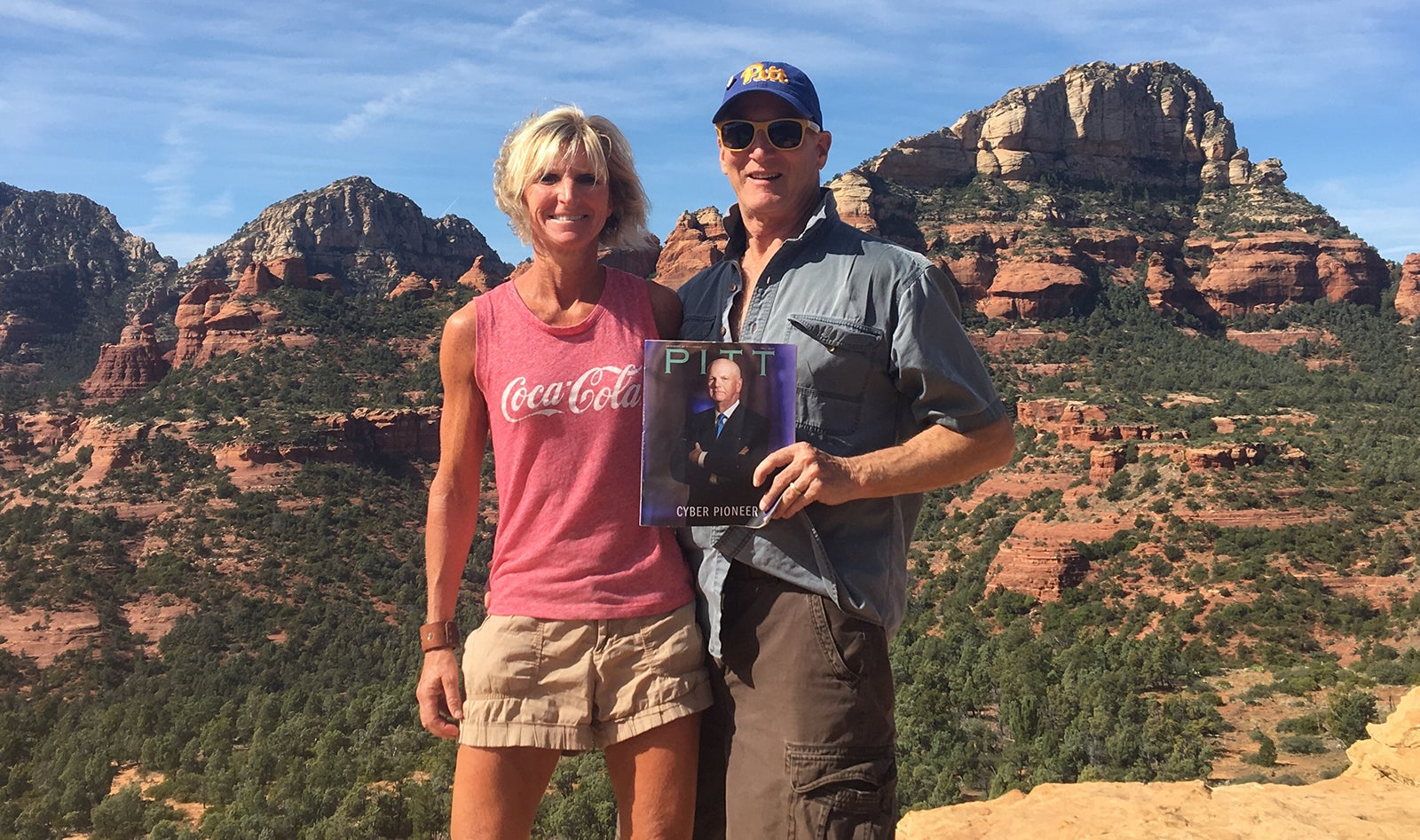 blond-haired woman in shorts and Coca-Cola tank top and man in short-sleeves and Pitt script hat hold Fall 2019 issue of Pitt Magazine in front of rocky landscape