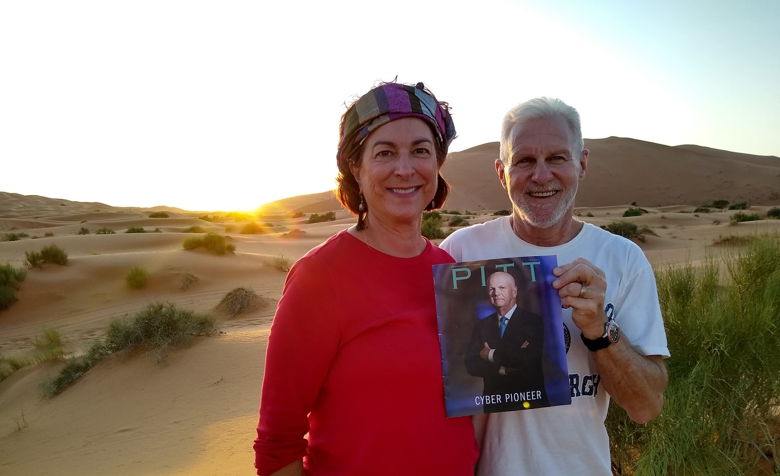 woman in red shirt and headband and man in white University of Pittsburgh T-shirt hold Pitt Magazine Fall 2019 issue as the sun goes down on sandy desert landscape