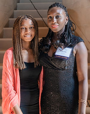 Omolara wearing a salmon cardigan and black dress and Aisha wearing a black lace dress, standing in front of steps inside Heinz Memorial Chapel