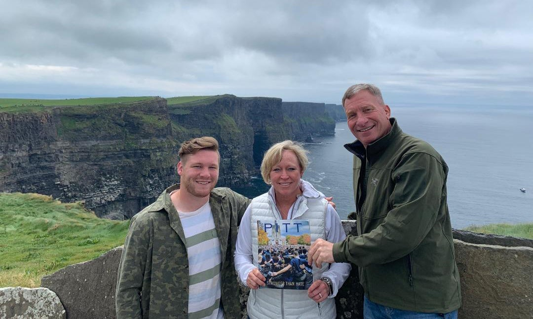 young man with his mother and father, dressed in greens and pale blue-grays, stand with Pitt Magazine Winter 2019 issue in front of the Cliffs of Moher