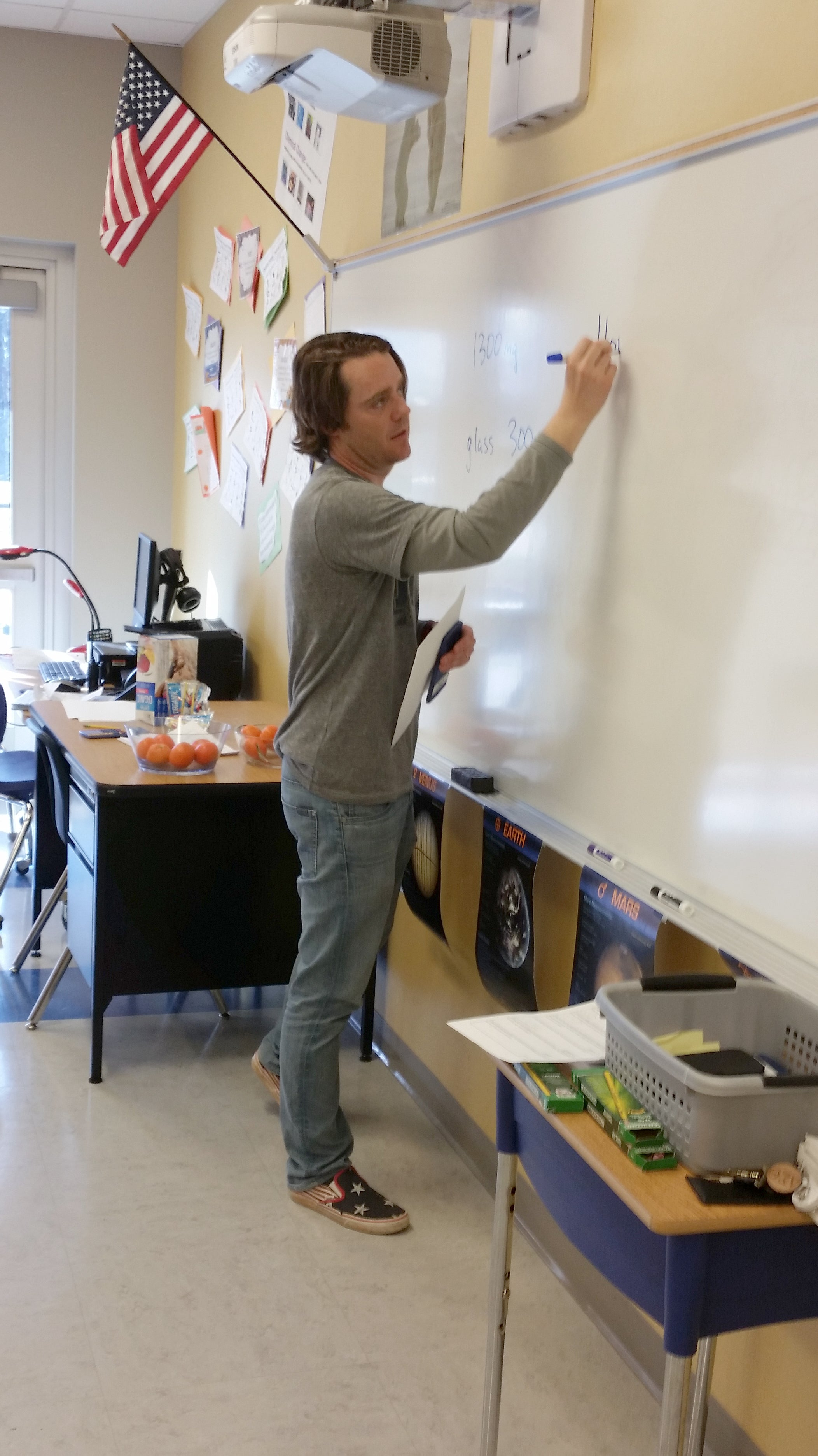 Andrew Van Fossen writes on a whiteboard in a classroom.