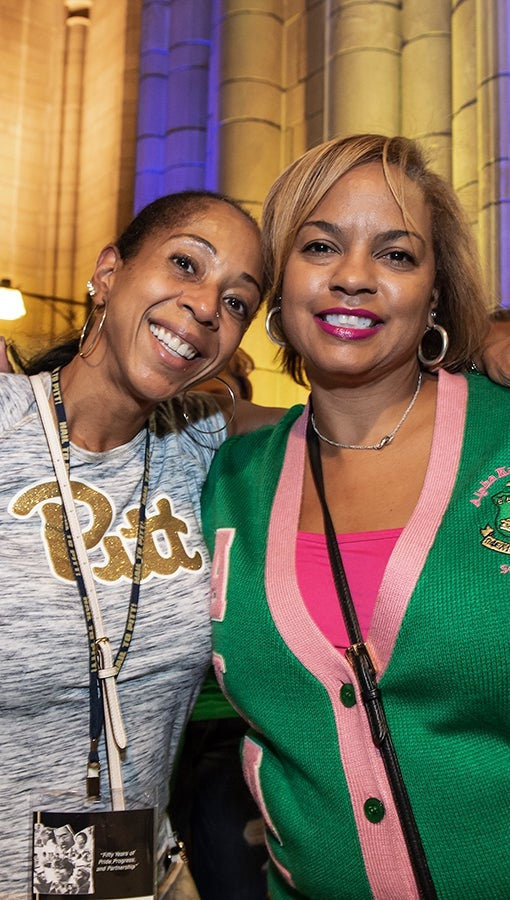 Tracy Floyd (left) and Carla Jackson meet up in the Cathedral of Learning during Homecoming week.