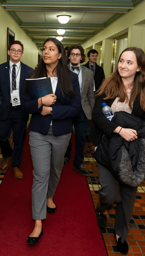 Pitt students in business wear walk down hallway together