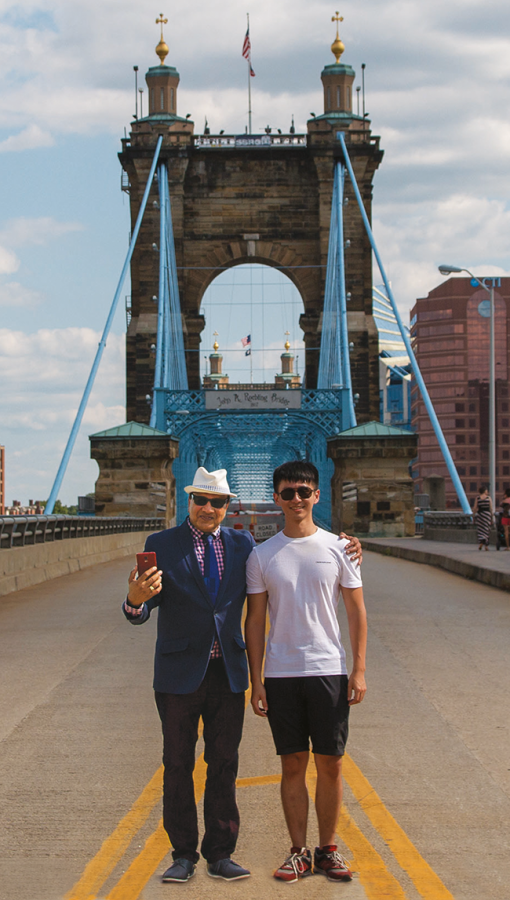 two men standing in middle of suspension bridge with bright blue detailing