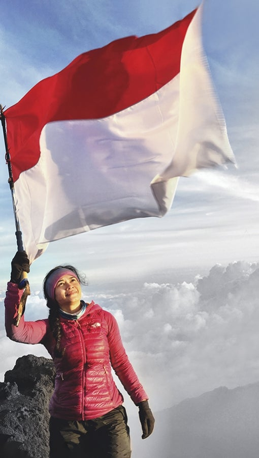 Diansyah Putri Handayani waves the Indonesian flag on the top of Mount Kerinci