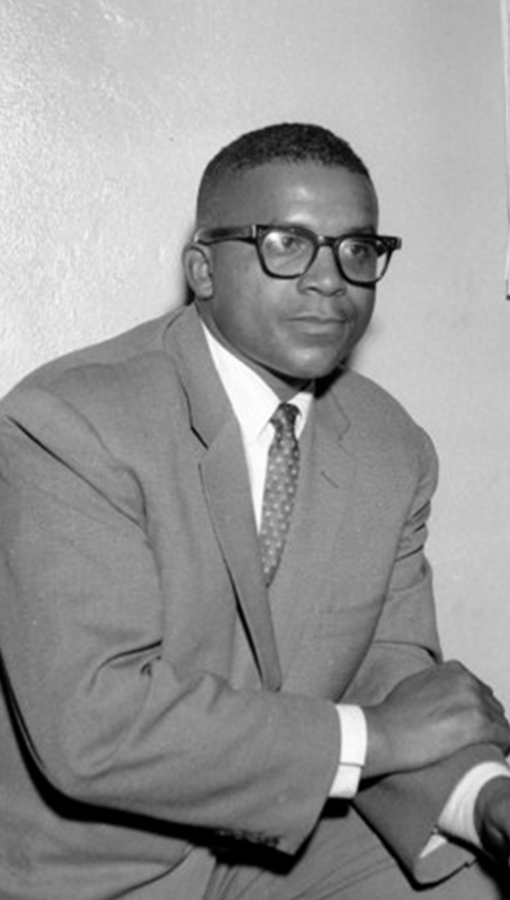 Young black man in suit and tie leans on knee, leg propped up, wears dark rimmed glasses