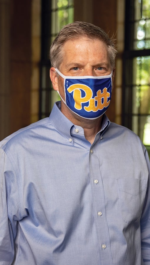Patrick Gallagher wears a Pitt script mask in his Cathedral of Learning office