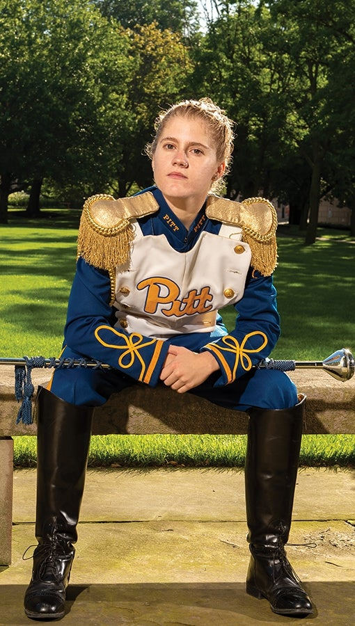 Pitt Band drum major Crissy Shannon sits in uniform in front of the Cathedral lawn.