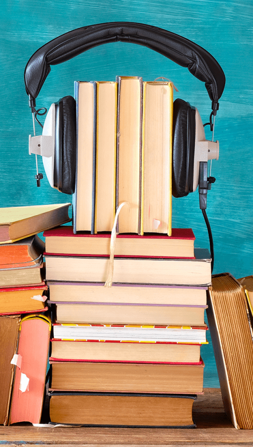 stacks of books, with over-the-ear headphones, on painted teal backdrop and wooden table
