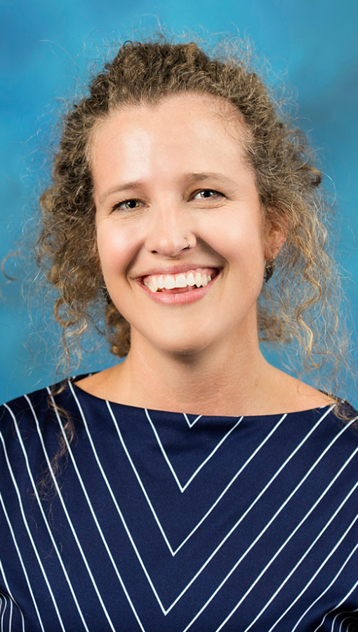 portrait of woman with curly light brown hair, wearing navy and white striped blouse, in front of teal background
