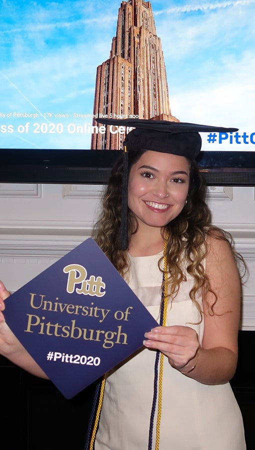 Oriana Garcia, with a mortar board and cords, celebrates her graduations from Pitt in her living room