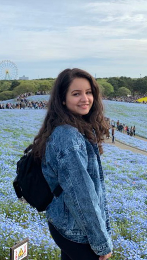 Young woman in denim jacket stands in field of small flowering blue flowers; lines of people, trees and a ferris wheel are visible in the background