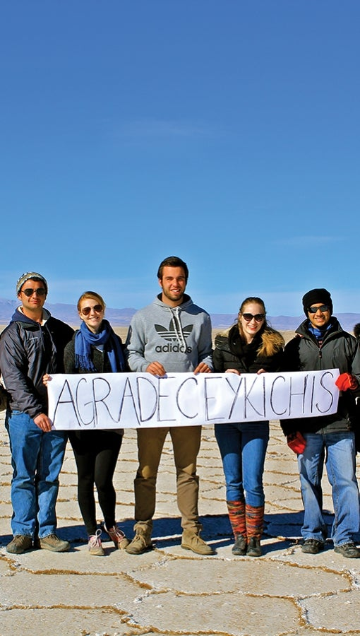 "Kevin Rieth, far left, and peers hold sign that reads ""Thank you"" in Quechua while visiting the Salar de Uyuni in Bolivia."