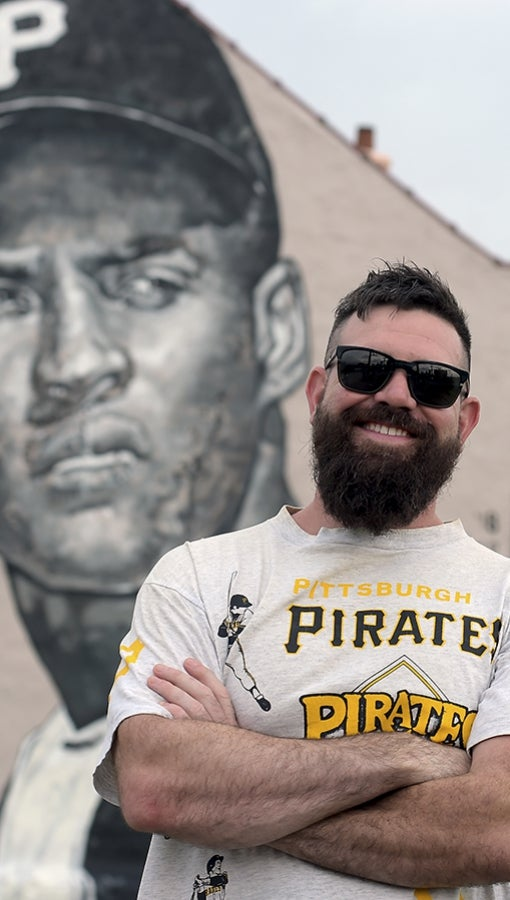 Jeremy M. Rayber stands in front of his mural of Pittsburgh Pirates Hall-of-Famer Roberto Clemente