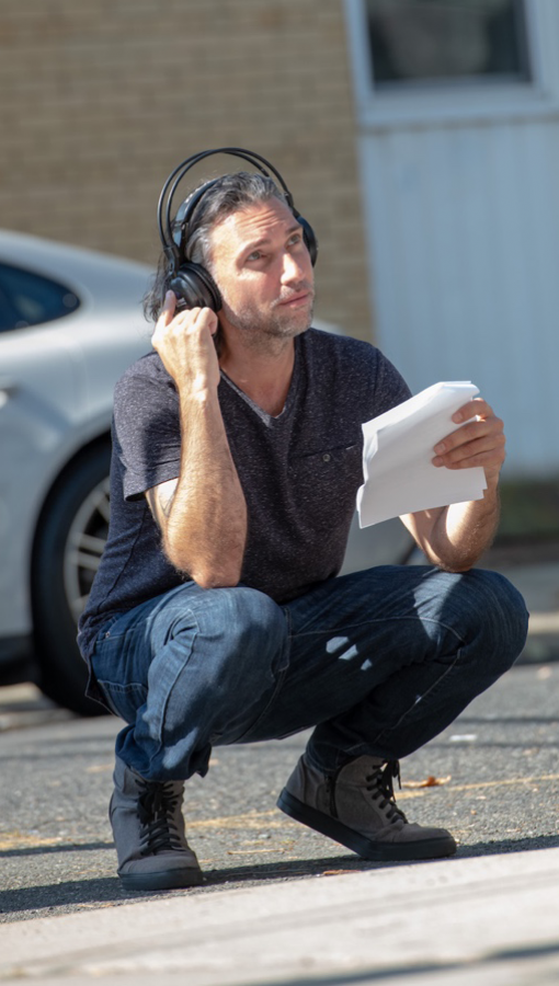 Man with shoulder-length silver hair, wearing jeans and dark t-shirt, crouches on pavement and holds earphones on head while looking in front of/above him