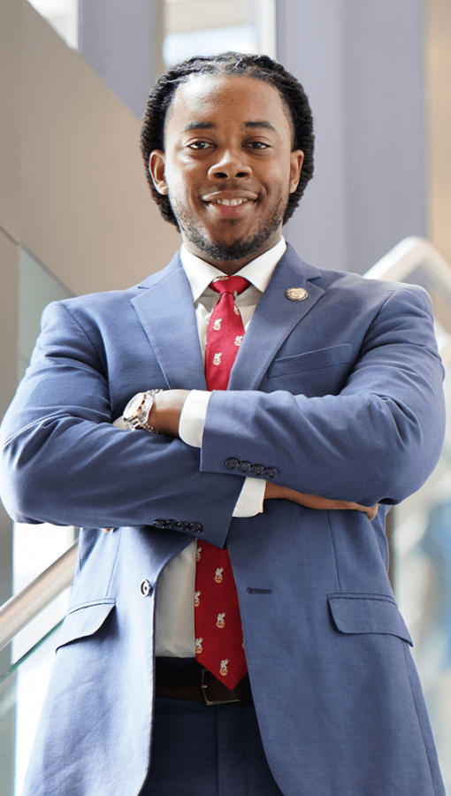 professional portrait of young Black man in blue-grey suit, white button-down shirt, red tie, standing in sunny stairwell, with arms crossed