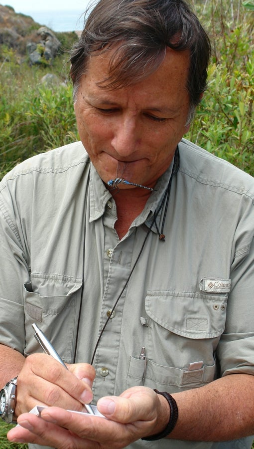 man with dragonfly specimen makes field notes