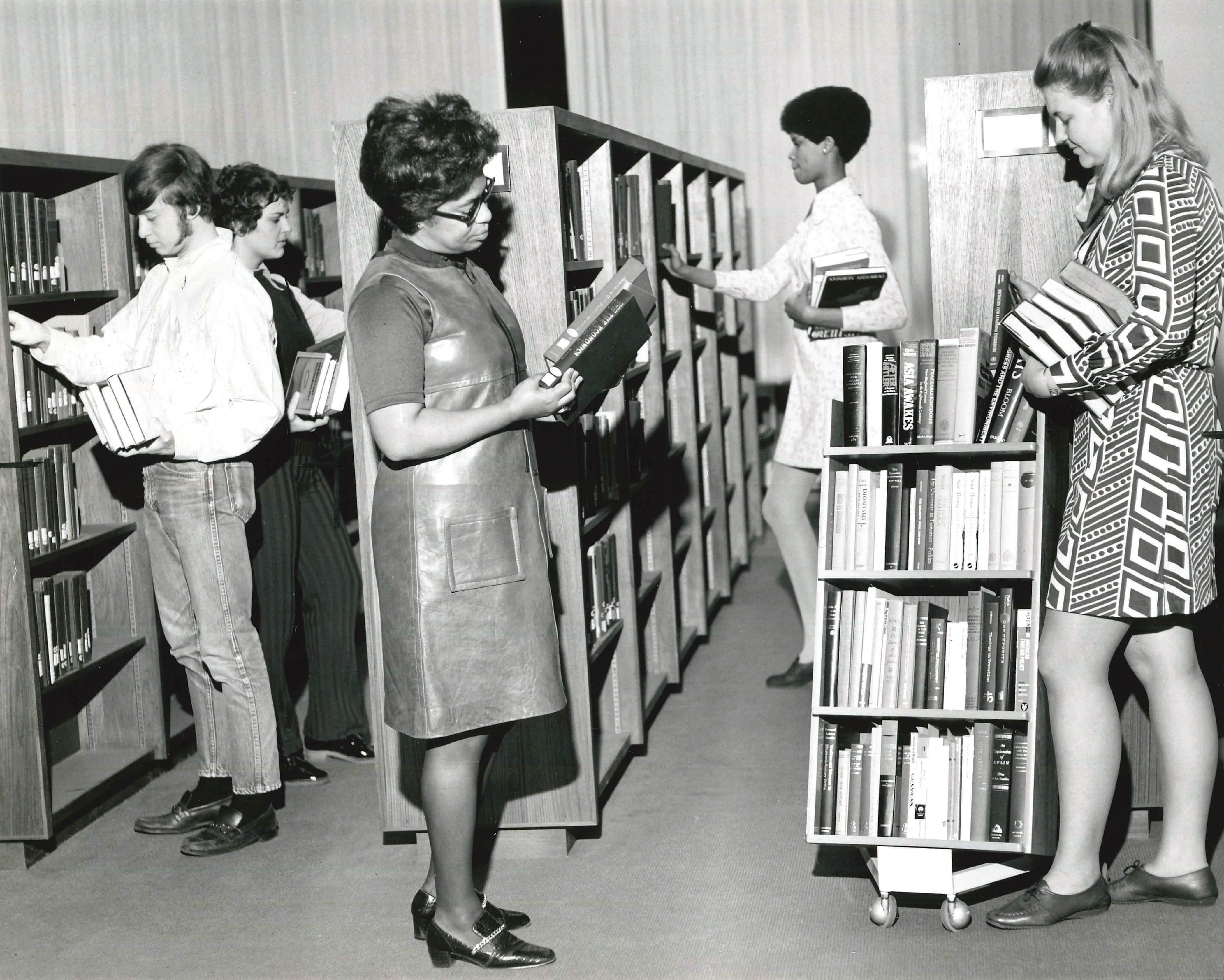 Librarians and work study students shelve newly acquired books in November 1970.