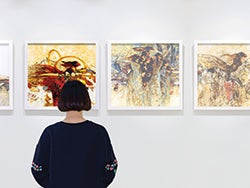 A woman looks at abstract art on the wall
