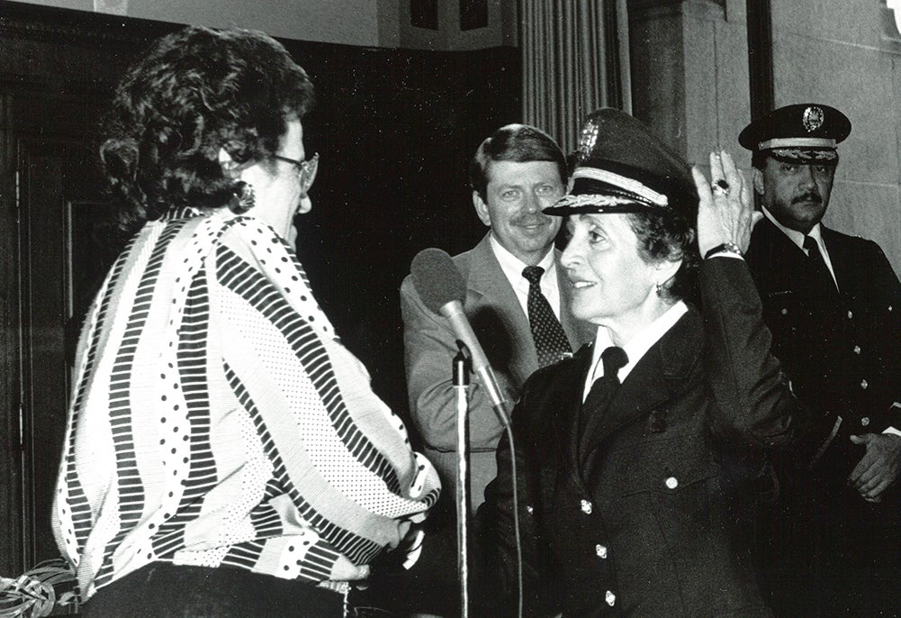 Rocco is sworn in in her police dress uniform, her left hand raised