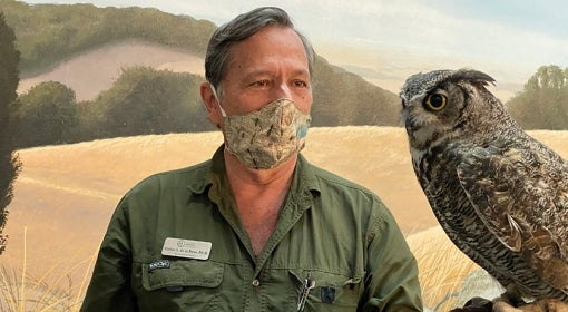 masked man holds great horned owl in front of painted field scene
