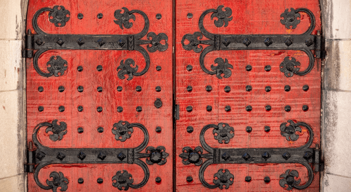 red wooden doors with ornate black iron studs and hinges