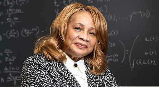 Elayne Arrington stands in front of a blackboard with math equations written in white chalk