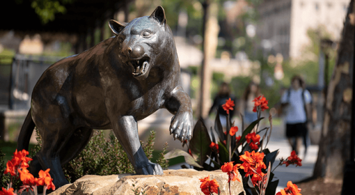 Panther statue with bright orange-red flowers, students walking in background