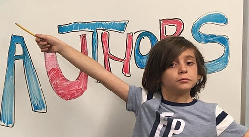 third grade student at Almost Authors points to welcome sign on whiteboard with pencil