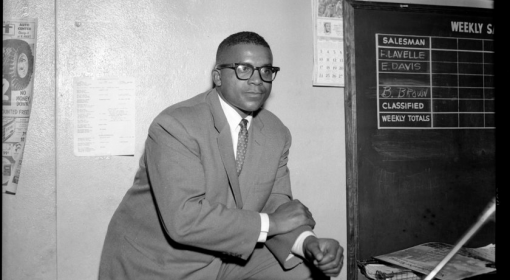 Young black man in suit and tie leans on knee, leg propped up, wears dark rimmed glasses in an interior space with chalkboard