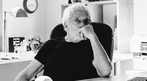 black and white photo of Lee Gutkind, in short-sleeved black t-shirt, sitting behind desk in his office