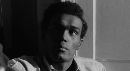 """screen still of Duane Jones as Ben in """"Night of the Living Dead."""" He is leaning back, and half of his face is in shadow"""