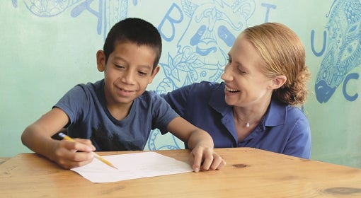 Emily Monroe helps a youngster with his writing at Casita Copán