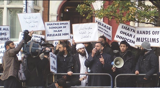members of the Emigrants hold protest on the sidewalk, with signs in English and Arabic