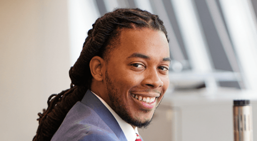 professional portrait of young Black man in blue-grey suit, white button-down shirt, red tie. He is smiling at camera.