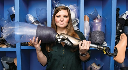 "Annie Kaitlyn Caulfield stands in front of what she and her colleagues call ""the graveyard,"" where parts of patients' old prostheses are kept."