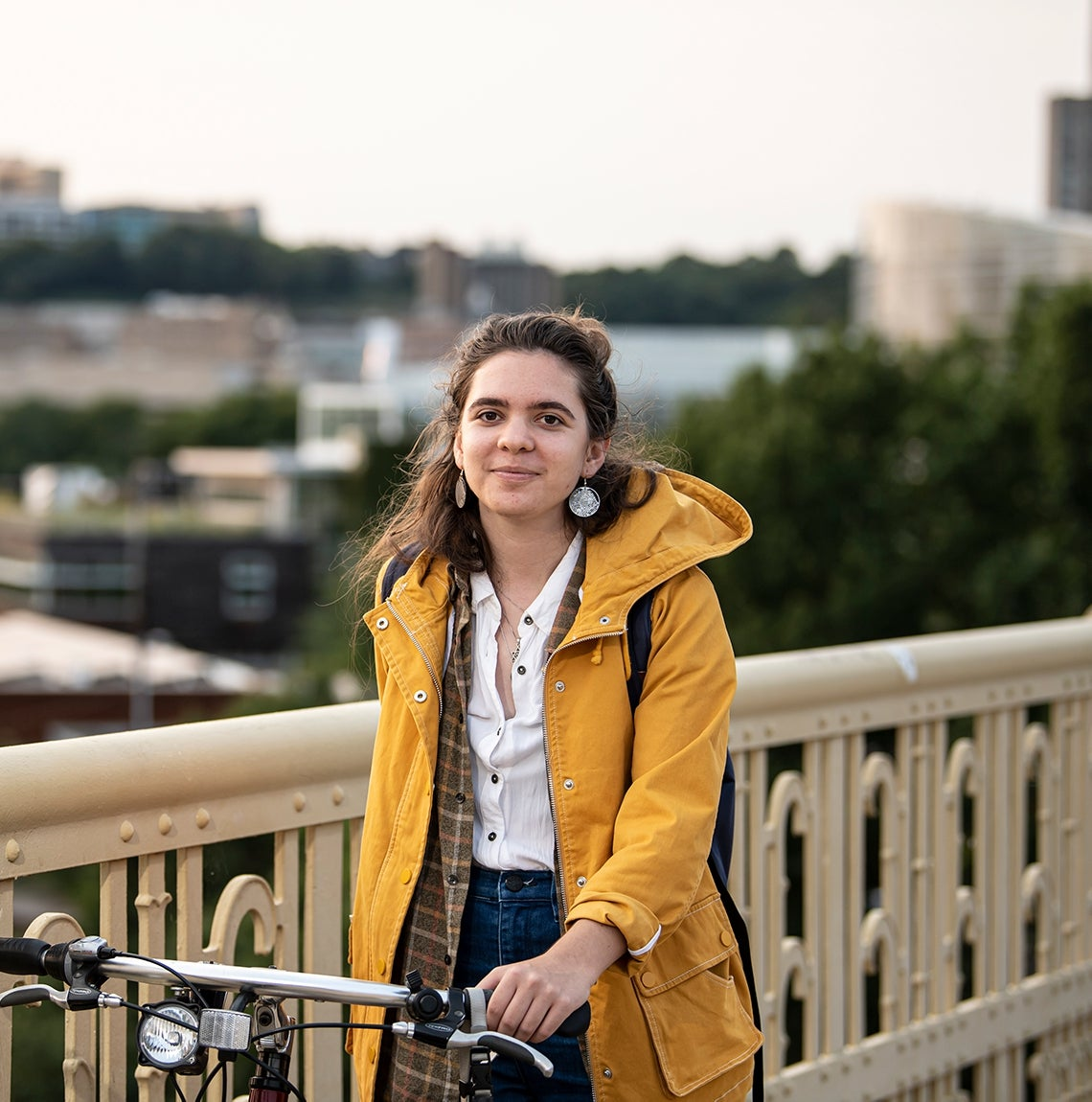 Avocet Greenwell, wearing a yellow coat, plaid shirt, a backpack, dangle earrings and jeans, stands on Schenley Bridge with her bike