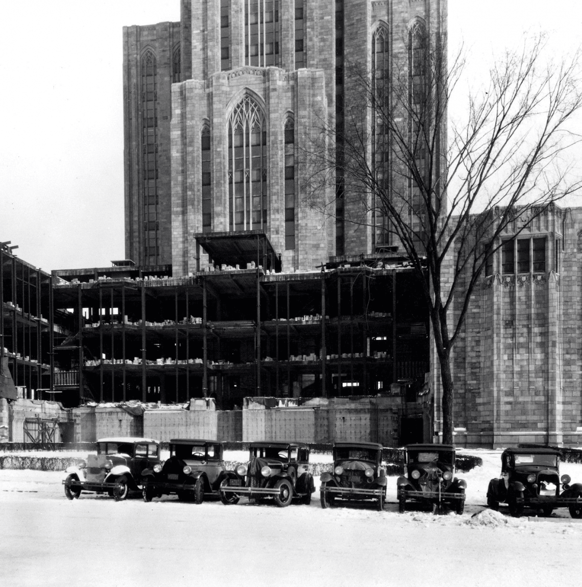 black and white photo of Cathedral with side under construction, old cars lined up in snow in front of it